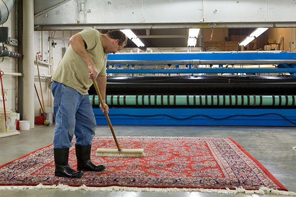 Each rug is meticulously brushed to set the pile before drying.