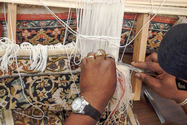 Complex weaving of a fine rug in progress.